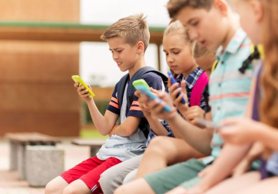 64166975 - primary education, friendship, childhood, technology and people concept - group of happy elementary school students with smartphones and backpacks sitting on bench outdoors